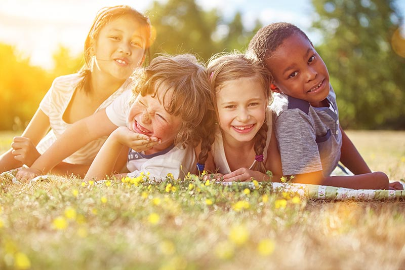 Children smiling out in the yard